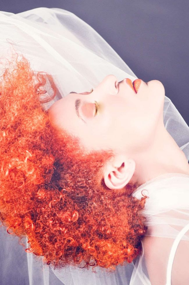Lady with orange Afro thinks about home hair dye