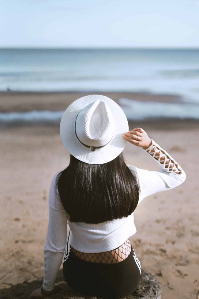 woman with black hair thinks about keratin treatments at home on the beach